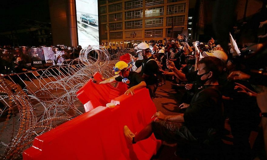 Anti-government protesters trying to break through police barricades in Bangkok yesterday. The rallies - led largely by youth who are calling for the Constitution to be amended, Thai Prime Minister Prayut Chan-o-cha to resign and the monarchy to be r