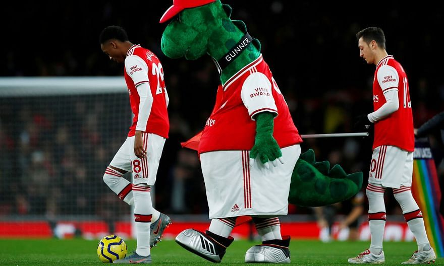 Mesut Ozil (right) and Arsenal club mascot Gunnersaurus are two figures who will not be involved in a match for the considerable future. Ozil has been left out of the club's Premier League and Europa League squads, while the dinosaur mascot was axed