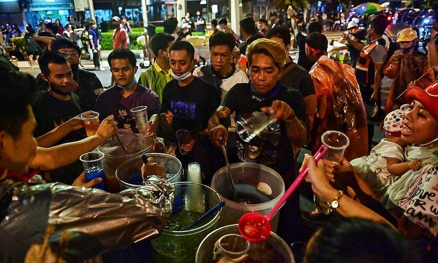 Pro-democracy protesters getting drinks from a street food vendor during an anti-government rally in Bangkok on Wednesday. PHOTO: AGENCE FRANCE-PRESSE