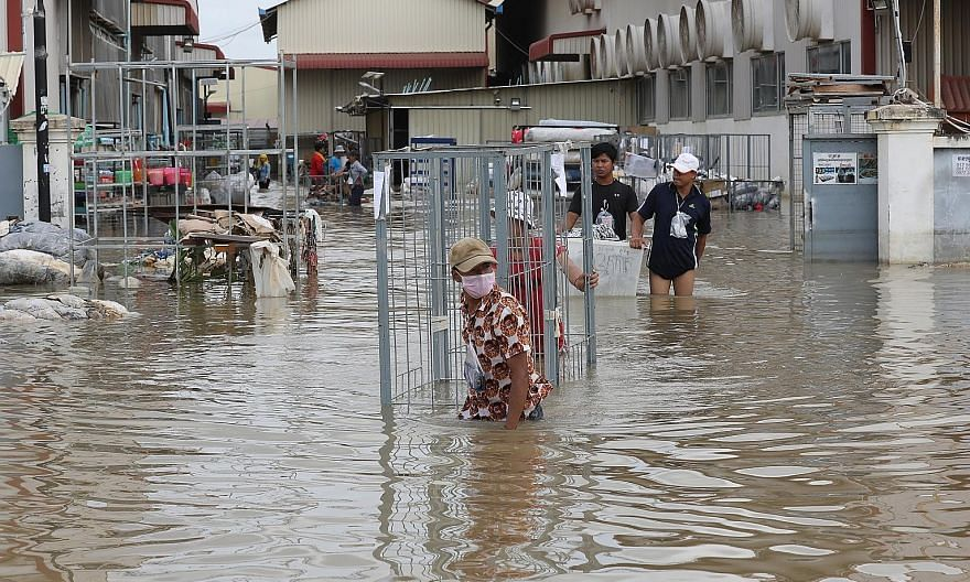 Garment workers gathering clothes from a flooded factory on the outskirts of Phnom Penh, Cambodia, yesterday. Cambodia, Vietnam and Laos have experienced heavy rainfall since the start of this month, which has been exacerbated by the arrival of tropi