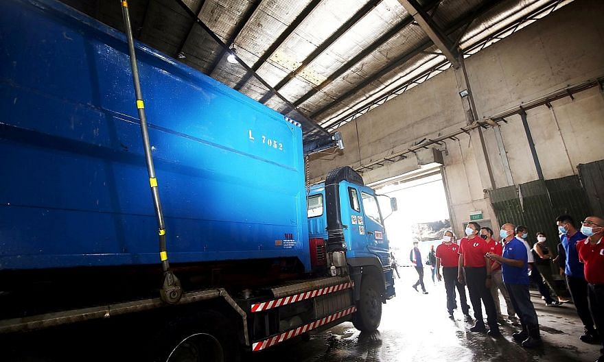 NTUC secretary-general Ng Chee Meng (second from left) and other union representatives observing a garbage truck, which is fitted with a device to unfurl a net to prevent trash from flying out in transit, during their visit to waste management firm W