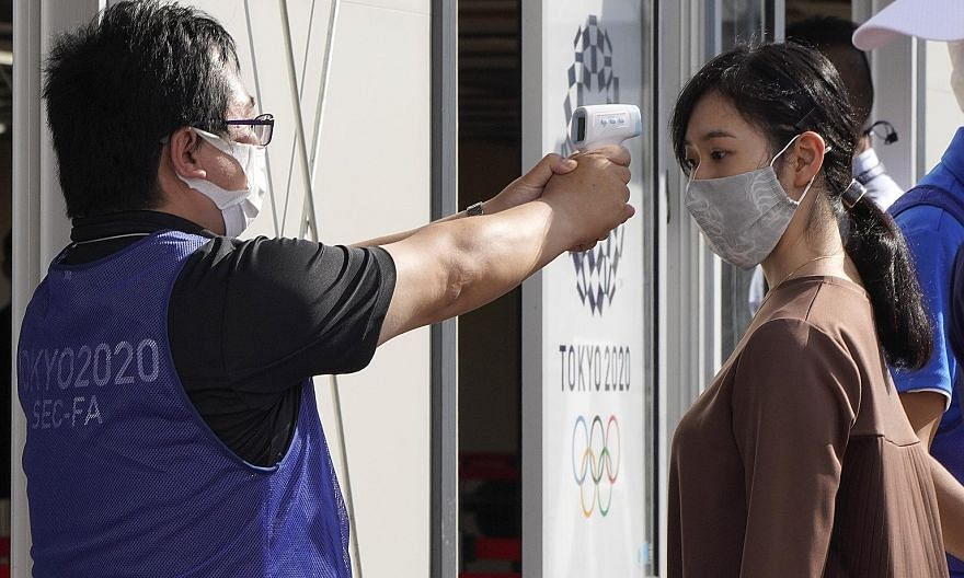 Security personnel measuring the temperature of a volunteer during a testing session at the Tokyo Big Sight convention centre on Wednesday. The screening measures are part of an effort to ensure the safe running of the Olympic Games, which are due to