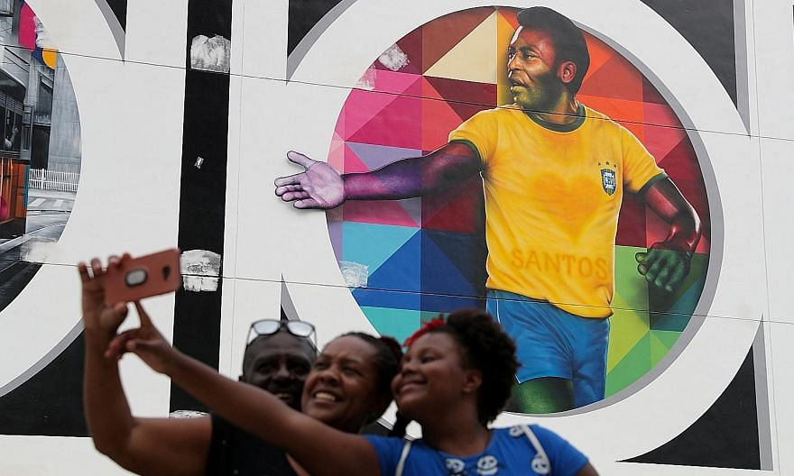 Fans taking a wefie in front of a mural depicting Brazilian legend Pele in Santos on Tuesday. The footballer turns 80 today. PHOTO: REUTERS