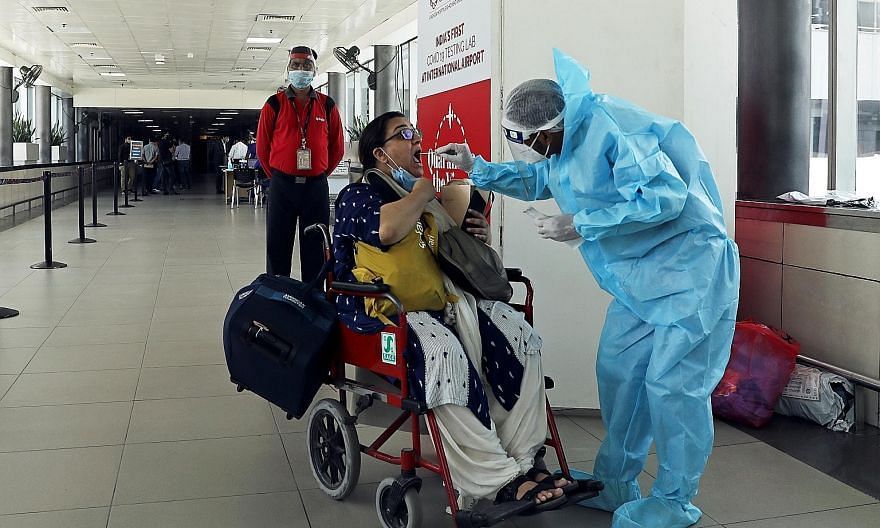 A woman being swabbed for Covid-19 at Indira Gandhi International Airport in New Delhi last month. All existing visas - except electronic visas, tourist visas and medical visas - will be restored, the Indian government said.