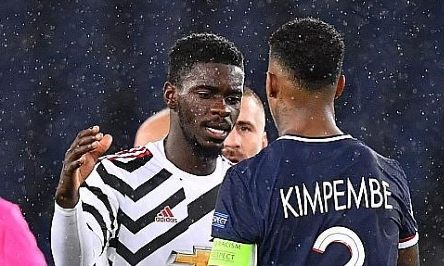 Manchester United's Axel Tuanzebe shaking hands with Paris Saint-Germain defender Presnel Kimpembe during their Champions League match on Tuesday. Tuanzebe could keep his place when United face Chelsea today.