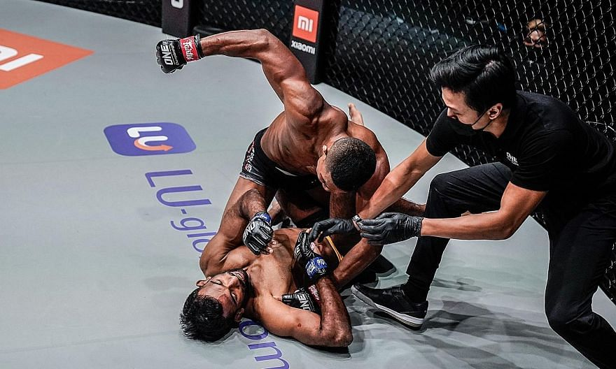 Singaporean fighter Amir Khan (top) taking on India's Rahul Raju at One Championship's Reign of Dynasties closed-door event at the Singapore Indoor Stadium on Oct 9. For next Friday's Inside the Matrix event, fans will need to take an antigen rapid t