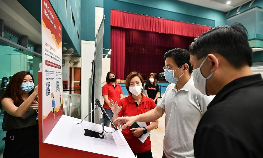 Education Minister Lawrence Wong talking to Ms Ong Shu Pei (in red), e2i's assistant director of hospitality and wellness, during a visit to the North West SkillsFuture Marketplace at Yew Tee Community Club yesterday. ST PHOTO: LIM YAOHUI