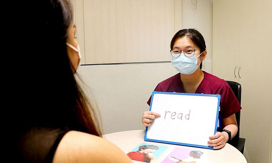 Ms Weng Wanxin (left), a senior speech therapist at Alexandra Hospital, conducting a therapy session for a patient with aphasia. The task involves matching a written word to a picture, which trains reading comprehension.