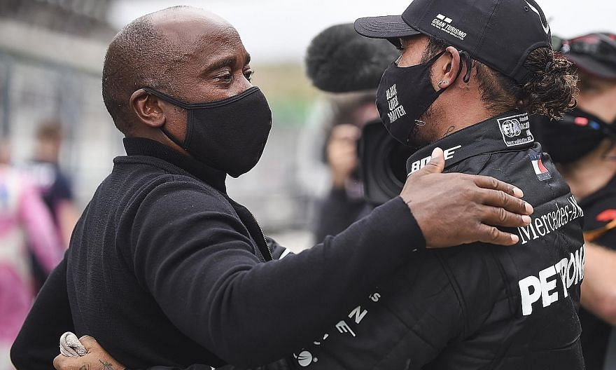 Six-time Formula One champion Lewis Hamilton and his father, the man behind his success, hug after he won the first Portuguese Grand Prix in 24 years yesterday at the Algarve circuit. PHOTO: EPA-EFE