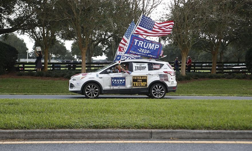 Above: A motorist on the move to show his support for President Donald Trump during his campaign stop at The Villages Polo Club in The Villages, Florida, last Friday. Below: