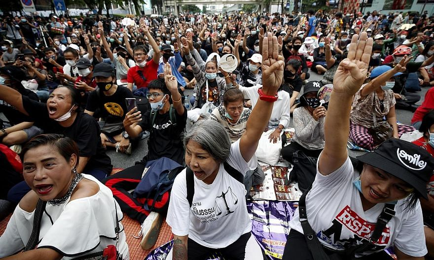 "Activists flashing a three-finger salute at an anti-government Bangkok rally yesterday. They want the premier to resign, a rewrite of the 2017 Constitution and the authorities to ""stop harassing"" political opponents. PHOTO: EPA-EFE"