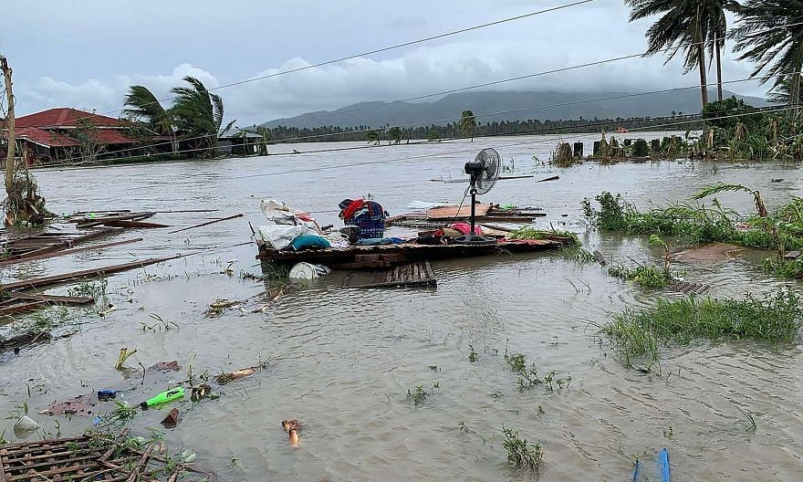 Above: The devastation left by Typhoon Molave in Pola, Oriental Mindoro province, yesterday. Left: Residents of the town heading back to their homes yesterday.