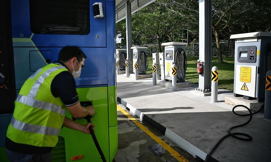 A Land Transport Authority officer showing how a fully electric double-decker bus is charged at Bulim Bus Depot in Jurong yesterday.