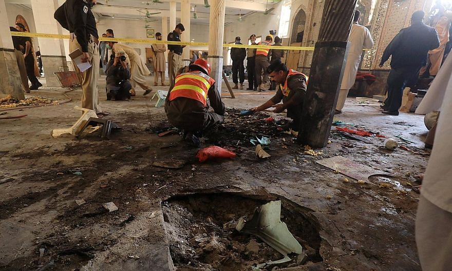 Investigators and workers searching for body parts at the site of a bomb blast at a religious school in Peshawar, north-western Pakistan, yesterday. A local hospital spokesman said seven bodies and 70 wounded people were taken to the medical facility