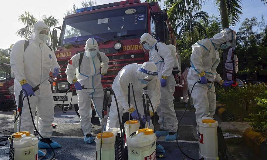 Firemen preparing to sanitise a building in Shah Alam, outside Kuala Lumpur, yesterday. Malaysia's third wave of coronavirus outbreaks has taken its toll on front-line workers, with up to 10,000 police personnel under quarantine and more than 200 pol