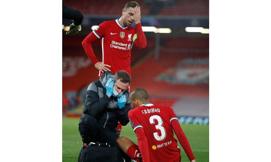 Left: Liverpool midfielder Fabinho receiving treatment after an injury in the 2-0 Champions League win over Midtjylland on Tuesday, as captain Jordan Henderson holds his head in concern. Below: Rhys Williams, the 19-year-old Liverpool centre-back, vy