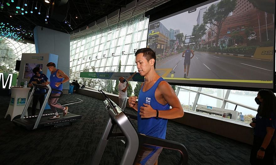 Keith Tan (right) and Lim Teck Yin, chiefs of the Singapore Tourism Board and Sport Singapore respectively, trying the augmented reality run on treadmills yesterday. The treadmills were affixed with tablets tracking runners' avatars on a virtual run