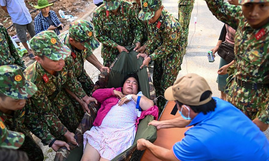 Above: Workers clearing debris following a landslide in central Vietnam's Quang Nam province. Right: Soldiers moving an injured woman onto a stretcher after she was rescued from a landslide in Tra Leng commune in Quang Nam yesterday.