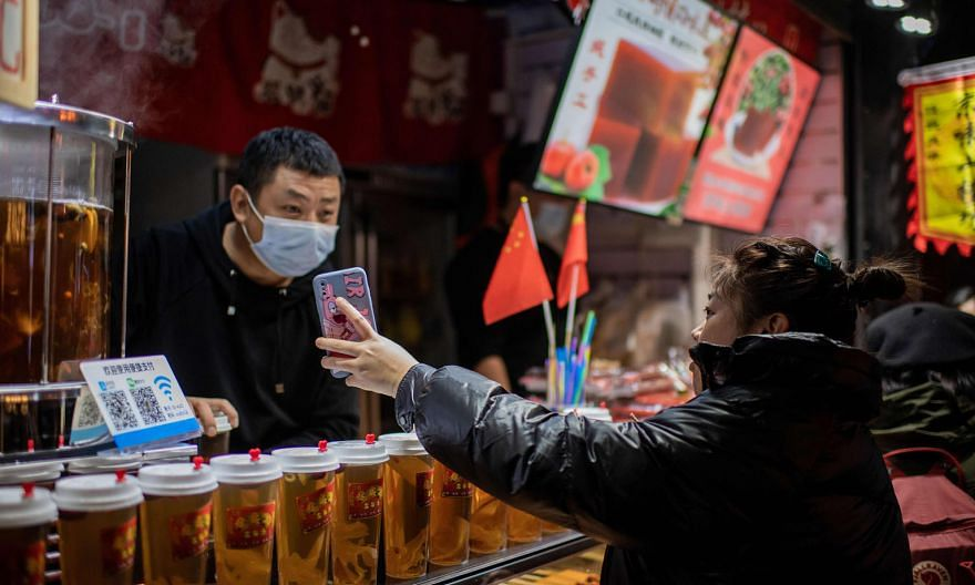 A customer displaying her Alipay electronic payment confirmation to an employee at a beverage shop in Beijing on Wednesday. China has revolutionised e-commerce and has raced ahead in the fields of artificial intelligence and 5G development, among its