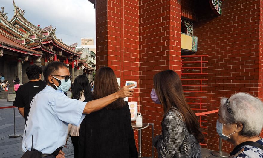 Above: Visitors to Xingtian Temple in Taipei getting their temperature checked. Except for wearing face masks and washing hands more often, life has returned to normal in Taiwan. Left: US Secretary of Health and Human Services Alex Azar wearing a fac