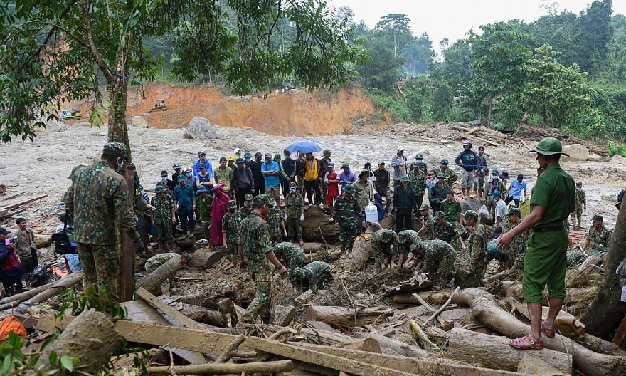 Left: A boy being comforted by a relative after losing his father in the landslides in Nam Tra My district in Vietnam's Quang Nam province yesterday. Below: Rescuers and residents searching yesterday for those missing after three landslides struck Na