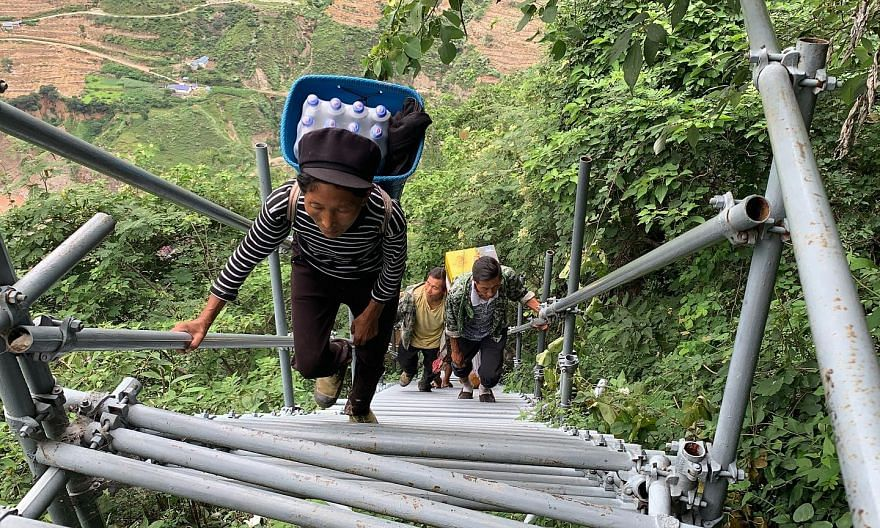 Villagers climbing a series of steel stairs and ladders (above) to reach their homes in the village of Atulie'er (left) in Liangshan Yi Autonomous Prefecture in Sichuan province. Officials acknowledge that the pandemic has badly affected the prefectu