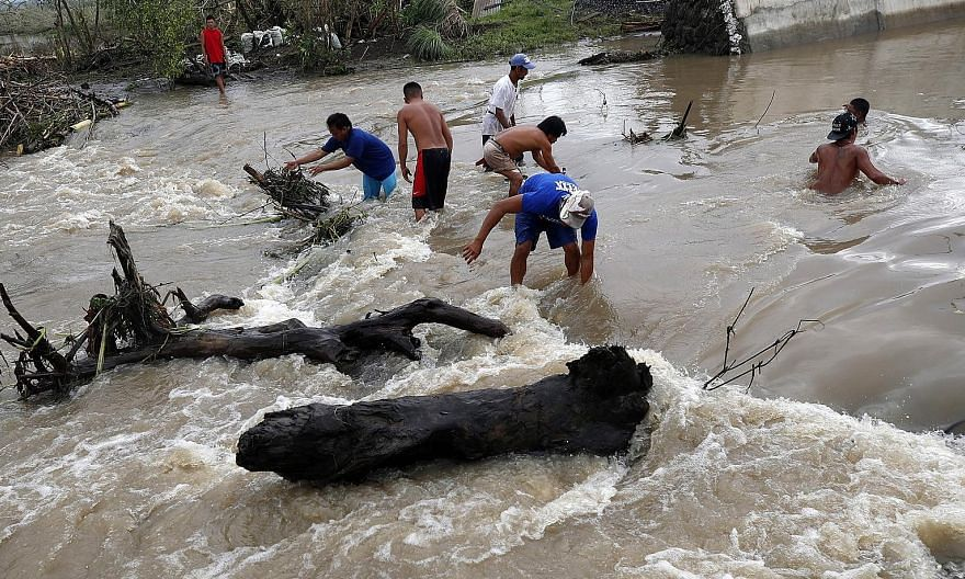 Debris being cleared after flood waters hit a town in Camarines Sur province yesterday.