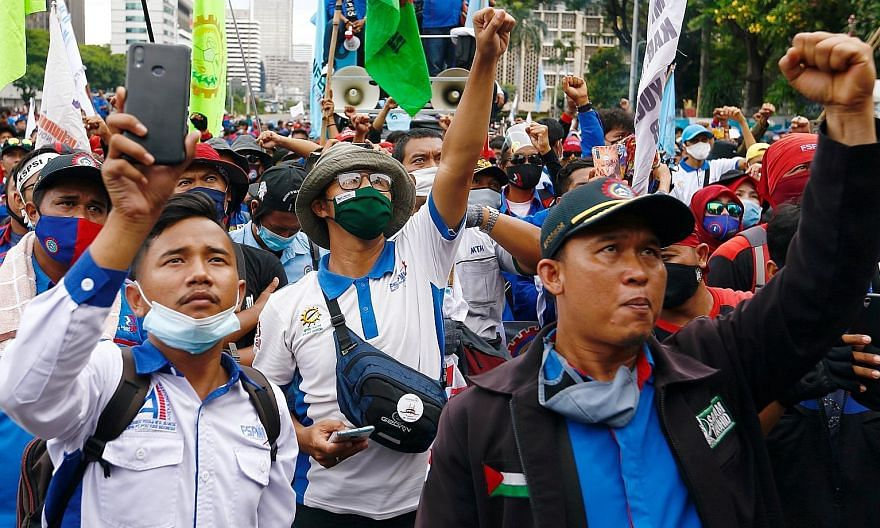 Indonesian trade union members protesting in Jakarta on Monday against the government's Job Creation Law. It was passed in Parliament on Oct 5 and signed off by President Joko Widodo on Monday. PHOTO: REUTERS