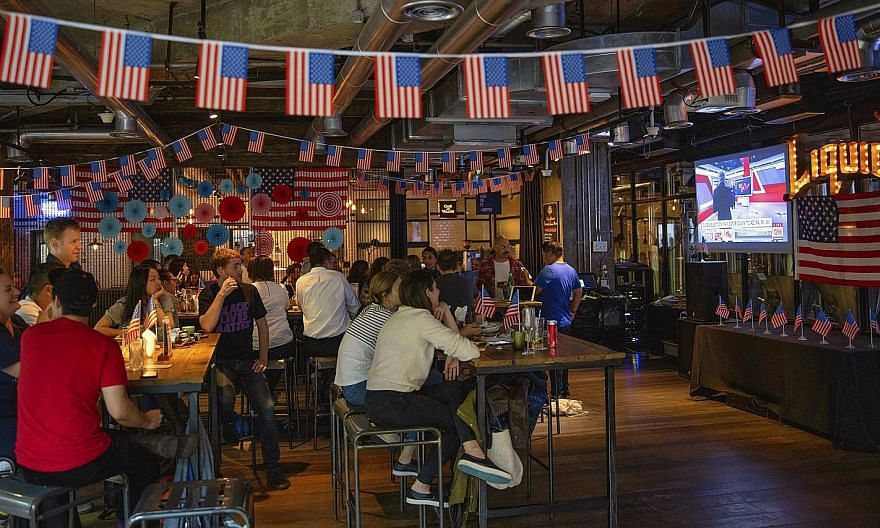 People tracking the US election results on television in a restaurant in Shanghai, China, yesterday. Crowds packed pubs and cafes for watch parties across Asia as the outcome of the presidential race remained uncertain.