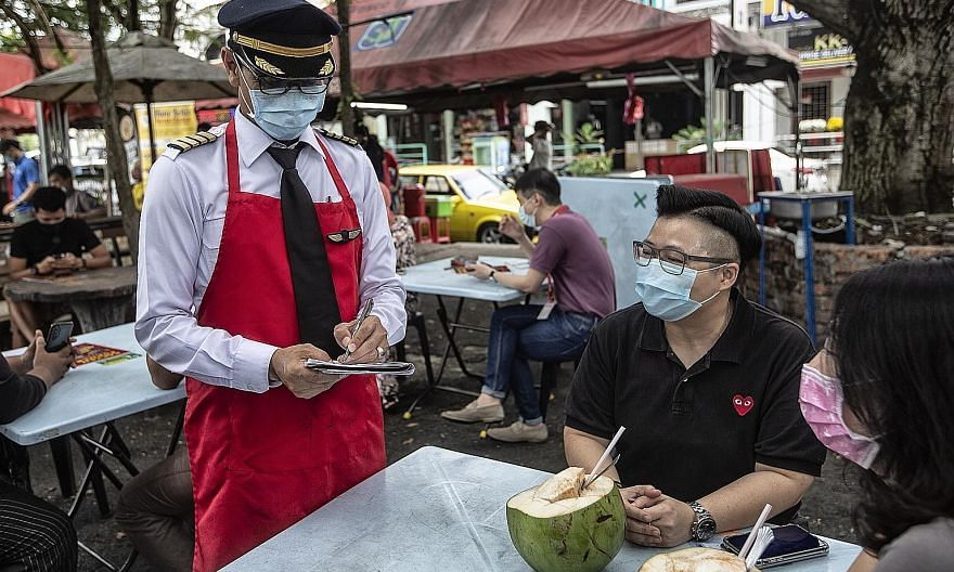 A Malindo Air pilot, who recently lost his job, taking orders at his food stall in Subang Jaya, Selangor. He is running the stall while waiting for the aviation industry to recover. Analysts say that among the budget's top priorities would be widenin