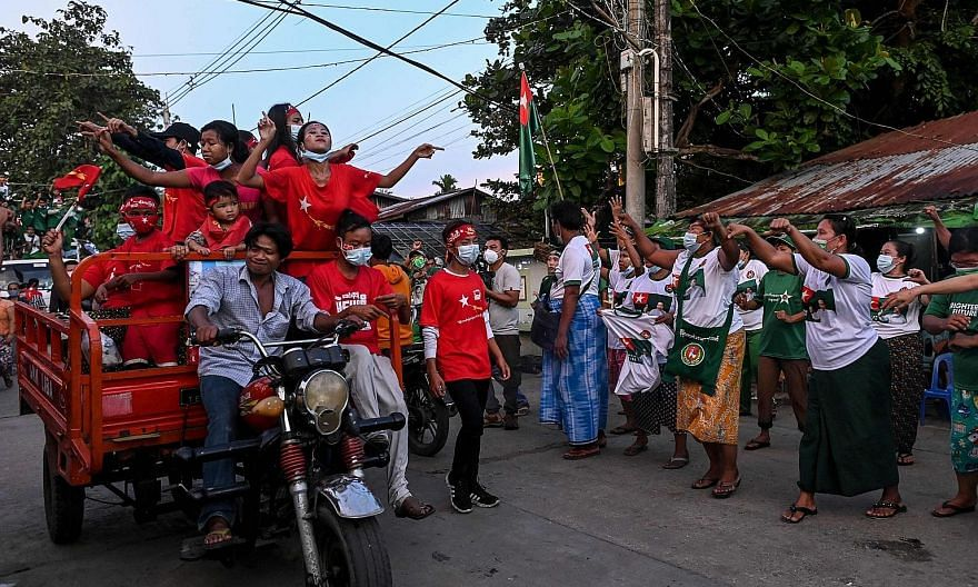 National League for Democracy supporters riding a trishaw decorated with party flags and images of Myanmar State Counsellor Aung San Suu Kyi outside Yangon on Friday. National League for Democracy (NLD) party supporters (in red) passing supporters of