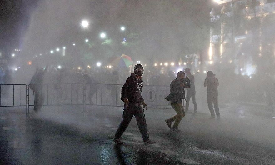 Protesters getting soaked after police deployed water cannon during a march to the Grand Palace in Bangkok yesterday. Demonstrators hauled along mock mailboxes for people to stuff letters to King Maha Vajiralongkorn.