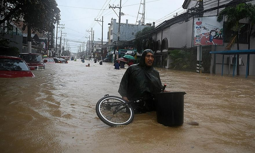A resident with his belongings making his way through a flooded street to get to a shelter, after Typhoon Vamco hammered Marikina city yesterday. PHOTO: AGENCE FRANCE-PRESSE