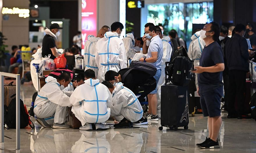 Passengers wearing isolation gowns on arrival at Changi Airport. The 11 new imported cases, of which two were symptomatic, tested positive while serving their stay-home notice. There were no new community cases and none from workers' dormitories. Wit