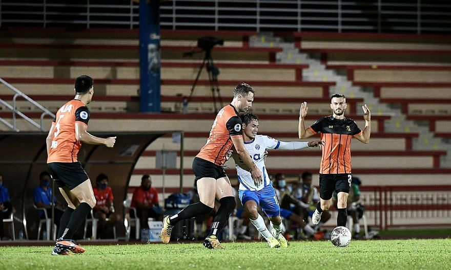 Hougang's Zac Anderson and Lion City's Gabriel Quak fighting for the ball in the penalty box during yesterday's SPL match at Hougang Stadium. Quak opened the scoring with a 12th-minute free kick.