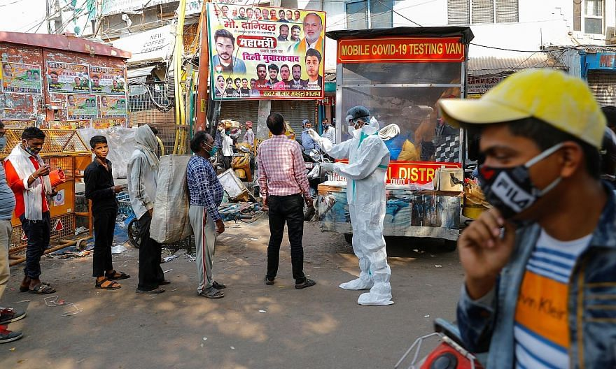 A healthcare worker in personal protective equipment collecting a swab sample from a man while others await their turn at a wholesale market in the old quarter of Delhi, India, yesterday. The city recorded 3,797 new cases on Monday, the highest numbe