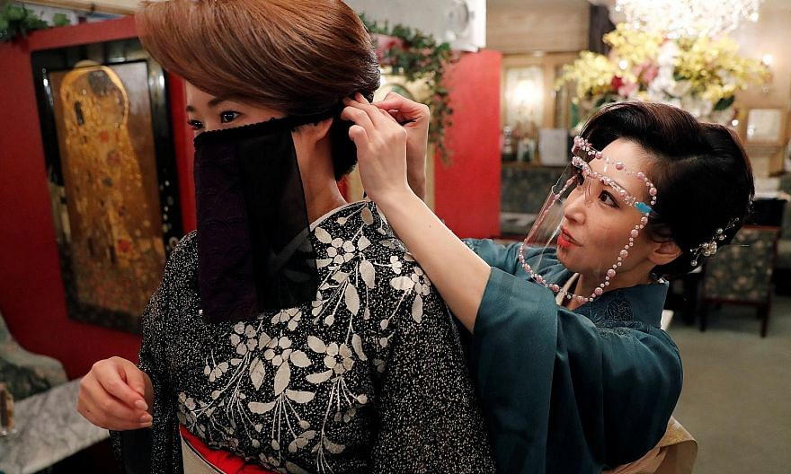 """A bar hostess helping another to wear a """"face veil mask"""" at a club in Tokyo on Monday. Japanese kimono maker Otoduki, which invented the mask, said it was inspired by the cloth masks worn by belly dancers, and it helps hostesses, dancers and musician"""