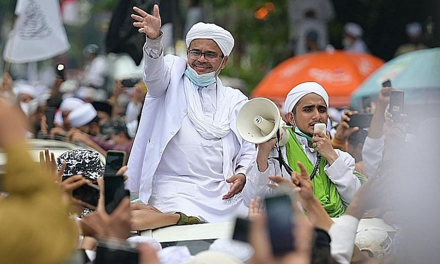 Cleric Rizieq Shihab greeting supporters in Jakarta on Nov 10 after returning to Indonesia from Saudi Arabia. Thousands turned out to greet him despite health protocols limiting gatherings to five people.