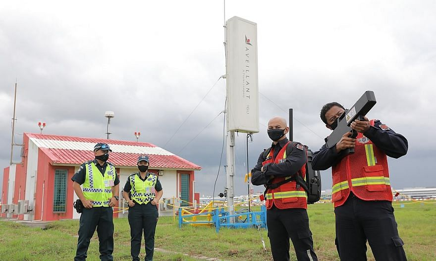 Ground enforcement officers (far left) and mobile disruption team officers next to the counter-unmanned aircraft system radar (in white), which is used to detect drones, at Changi Airport yesterday. The officer on the right is holding a radio frequen