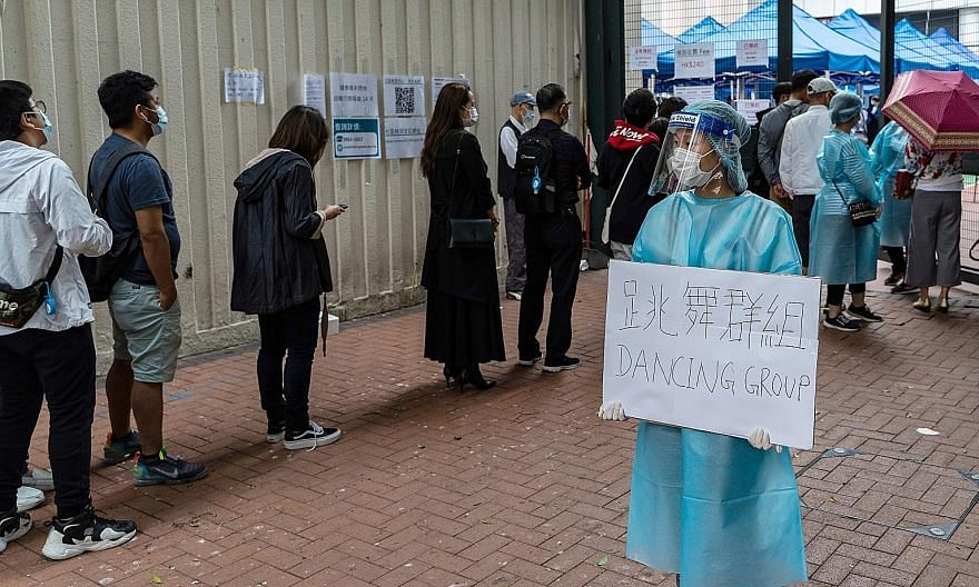A healthcare worker holding a sign referring to a dance studio cluster, as people waited outside a community testing centre in Hong Kong on Monday. The government yesterday issued a notice to say that seven more venues across the city had been added