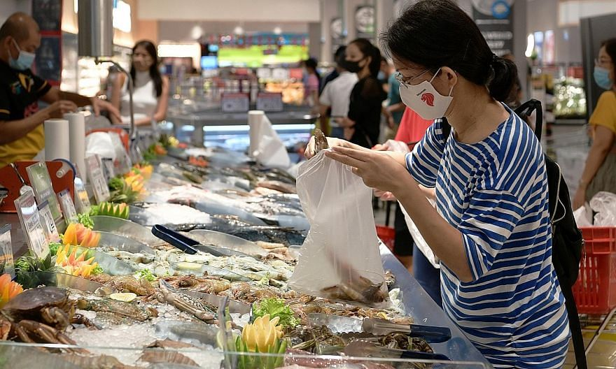 A customer selecting Red Sea shrimp at FairPrice Xtra at VivoCity. The shrimp - sold at $13.90 for 800g - are priced at a premium as they are known for their rich flavour, thanks to the Red Sea's high salinity compared with seawater elsewhere in the