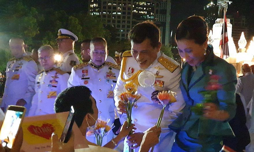 King Vajiralongkorn receiving flowers from a supporter. He greeted his adoring supporters after paying respects at a monument dedicated to his late grand-uncle, King Vajiravudh. Royalists waving flags and holding pictures of King Vajiralongkorn at Lu