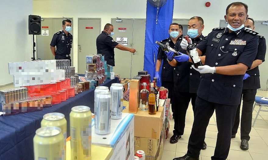 Shah Alam Assistant Commissioner of Police Baharudin Mat Taib displaying to the media a haul of liquor and cigarettes sold without proper permits at business premises. PHOTO: BERNAMA
