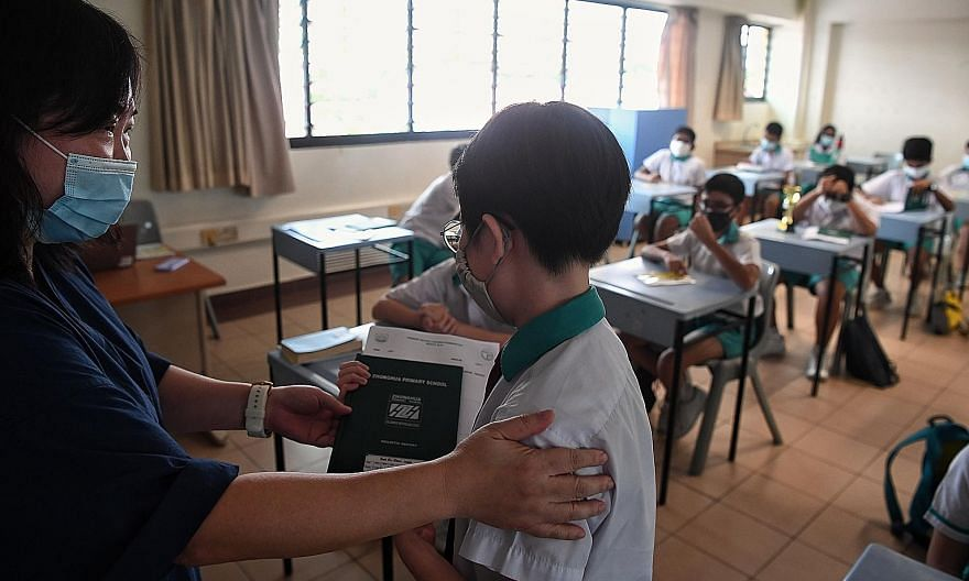Accompanying persons waiting in the hall of Zhonghua Primary School. Due to the young age of PSLE pupils, a parent or guardian was allowed to accompany the child or ward to school to collect the results. ST PHOTOS: KUA CHEE SIONG Pupils collecting th