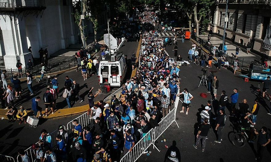 Thousands waiting yesterday to visit the funeral chapel of football legend Diego Maradona installed at the Casa Rosada in Buenos Aires. Above: Fans filing past the Argentinian football legend's casket. Right: Distraught fans embracing in the streets.