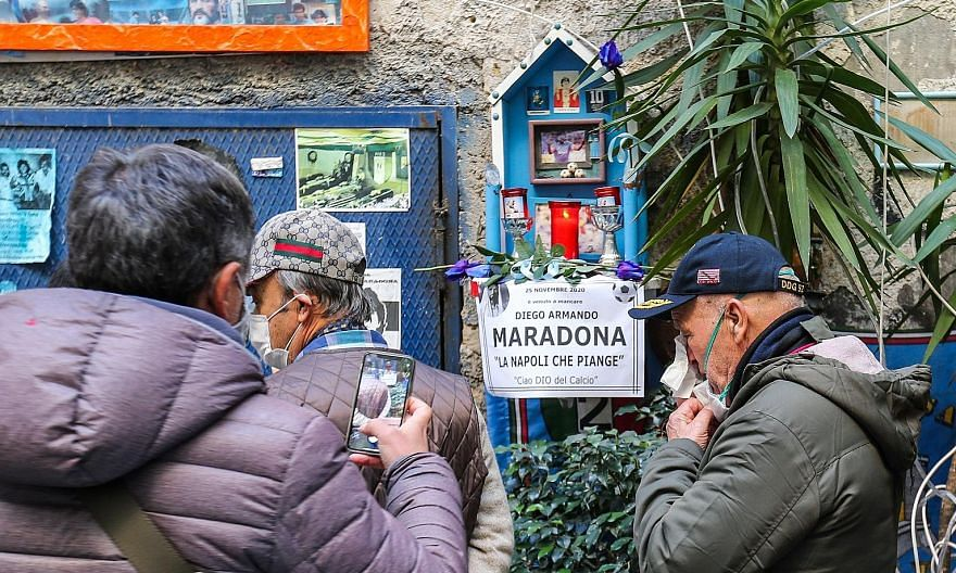 People gathering around an altar to mourn football legend Diego Maradona yesterday in the Spanish quarter of Naples, a day after his death from a heart attack in Argentina.