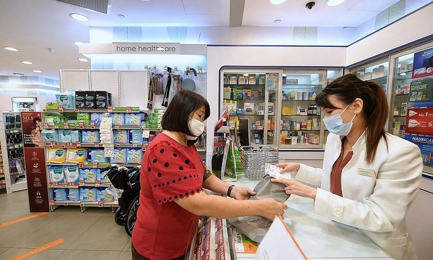 Retiree Yoo Bee Eng, 64, a caregiver to a patient of Singapore General Hospital, collecting the patient's medication from a Guardian store yesterday. ST PHOTO: NG SOR LUAN