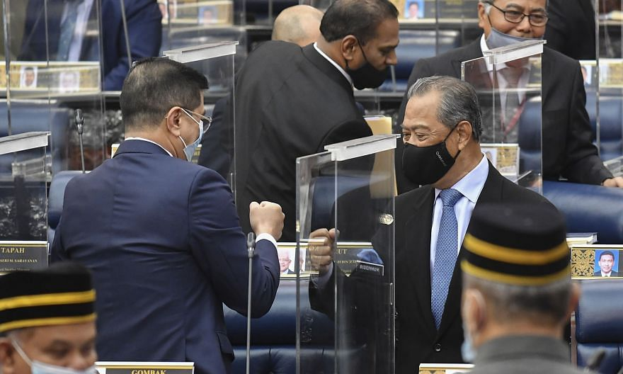 Malaysian Prime Minister Muhyiddin Yassin (right) exchanging a fist bump with International Trade and Industry Minister Azmin Ali after the parliamentary session in Kuala Lumpur yesterday. The PM is barely holding on to a majority, with just the need