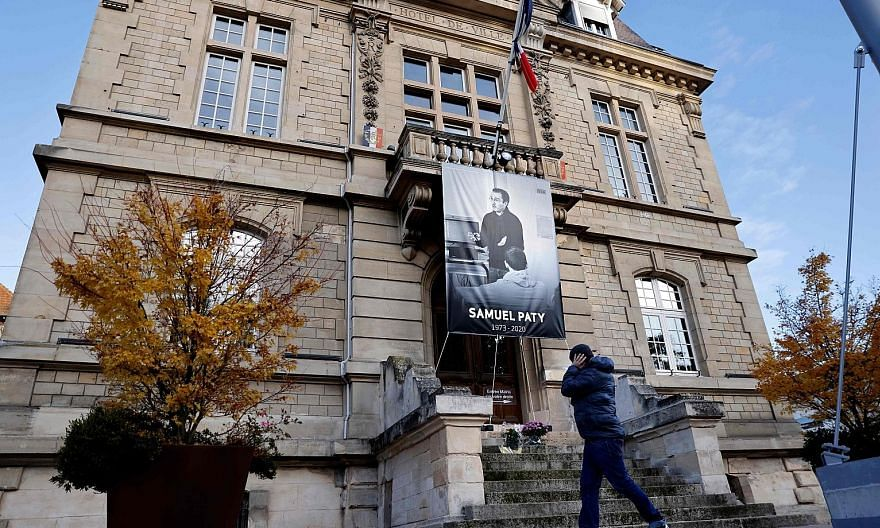 A poster of French teacher Samuel Paty on the facade of the City Hall building in Conflans-Sainte-Honorine. He was killed last month, days after showing his class caricatures of Prophet Muhammad that had been published by Charlie Hebdo a few years ag