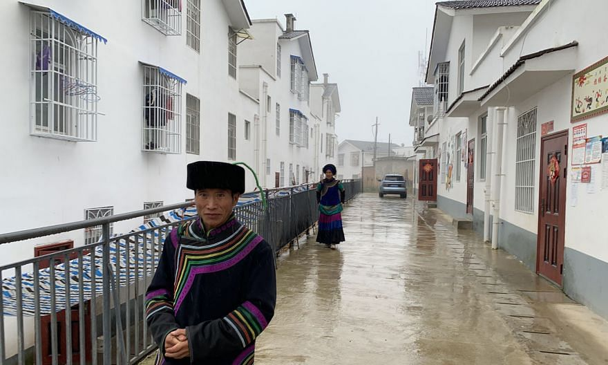 Right: Villagers walking down an alley between rows of new houses built by the Chinese government - as part of its anti-poverty campaign - in Xujiashan village in Liangshan Yi Autonomous Prefecture's Ganluo county. Villagers used to live in mud huts.